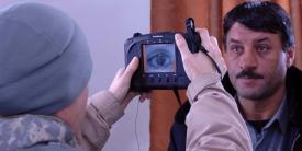 A U.S. airman photographs the iris of an Afghan district police chief. The images are cataloged in a database containing biometric information used to identify locals.