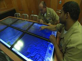 U.S. Navy personnel use an experimental mockup of a submarine situational awareness system based on Google Earth. Navy officials aim to begin deploying the geospatial information system on Virginia-class submarines next year.