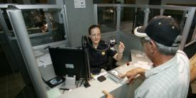 A Customs and Border Protection officer takes biometrics from an arriving foreign visitor. Integrating biometrics into the pre-arrival vetting process is one of the National Vetting Center's key tasks.  Customs and Border Protection