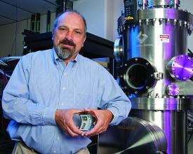 Eric Forsythe, Ph.D., team leader and flexible electronics display deputy project manager  with the Army Research Laboratory, poses with some of the equipment used to produce the flexible displays at the Army's Flexible Display Center at Arizona State University.