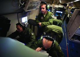 U.S. Air Force officers monitor moving target indicators during a training exercise for the Joint Surveillance and Target Attack Radar System (JSTARS).