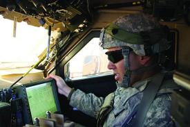 A U.S. Army soldier communicates inside his vehicle during the Army's Network Integration Evaluation (NIE) 12.2 in spring 2012.