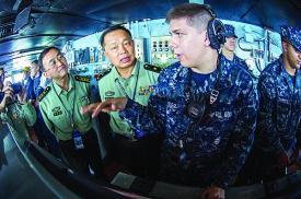 Seaman Alex Snyder, USN, right, explains the functions of the helm on the navigation bridge of the aircraft carrier USS George Washington to Maj. Gen. Chen Weizhan, deputy commander of the People's Liberation Army, Hong Kong Garrison, center, and Col. Li Jiandang, Hong Kong Garrison liaison officer during a distinguished visitor embark.