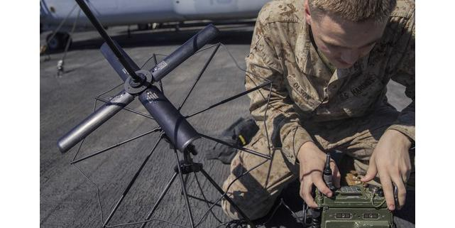 "A U.S. Marine Corps Lance Corporal is assembling an AN/PRC-117G radio on the flight deck of an amphibious assault ship. The Mobile User Objective System (MUOS) adds updated firmware to the radio, giving warfighters more advanced satellite communications."" Credit: U.S. Marine Corps photo by Lance Cpl. Tawanya Norwood."