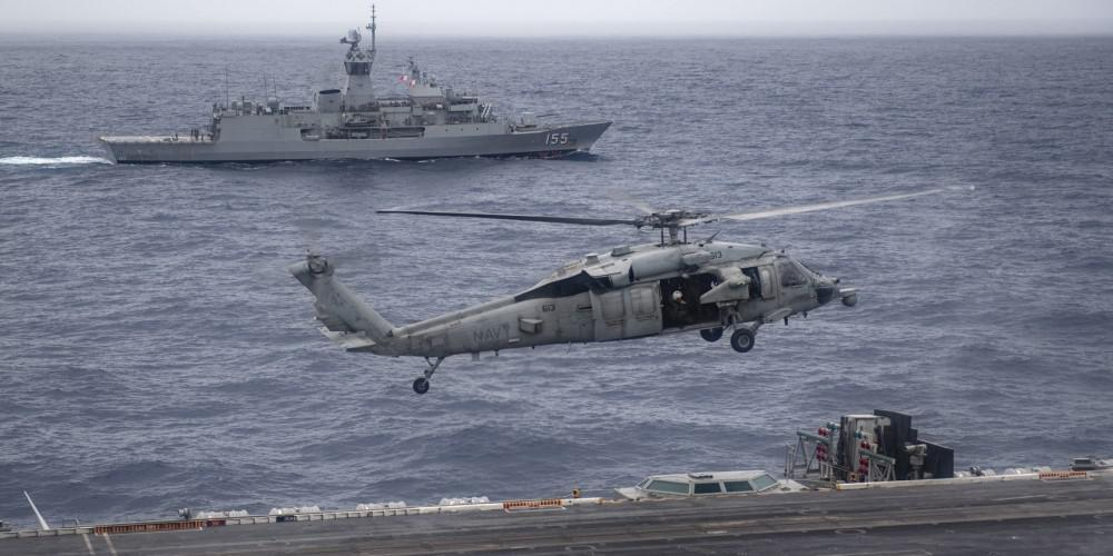 The Royal Australian Navy frigate HMAS Ballarat sails alongside the USS Nimitz as a U.S. Navy helicopter lands on the flight deck. The United States and its Indo-Pacific allies are working to improve their communications interoperability as they face growing challenges in the vast region. Credit: U.S. Navy