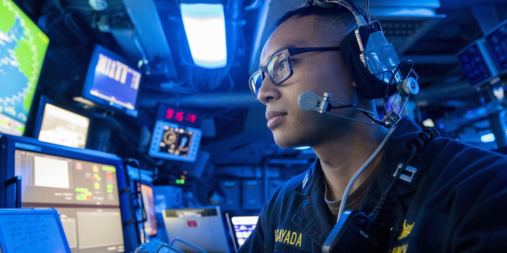 A U.S. Navy lieutenant stands watch in the command control center aboard an amphibious transport dock ship as part of the Boxer Amphibious Ready Group and 11th Marine Expeditionary Unit team. The Navy and the Marine Corps are undertaking a rebuild of their information technology capabilities in the face of increased global threats.
