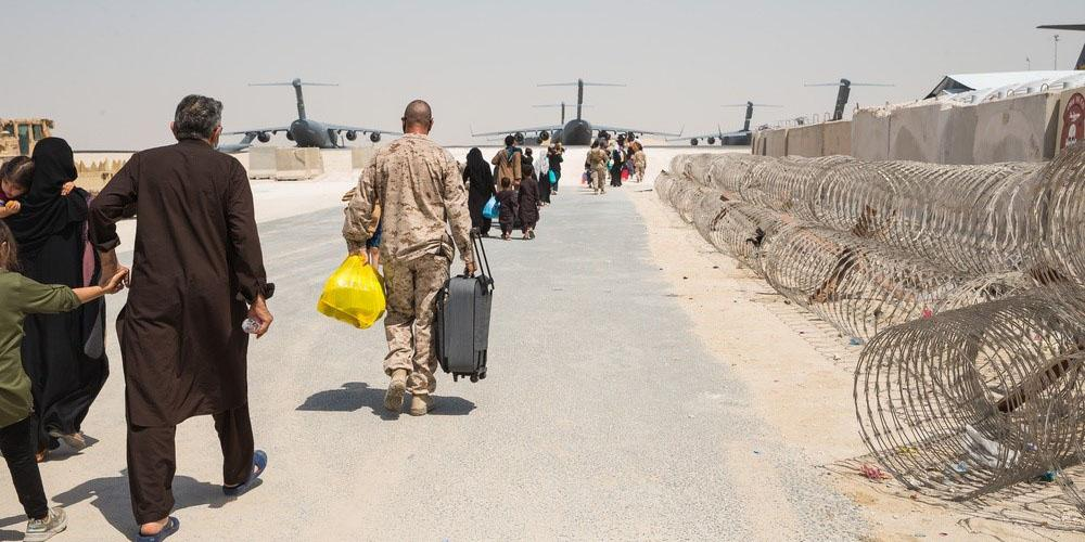 Master Sgt. Michael Lesterick, USMC, carries an Afghan evacuee's luggage as they board a plane at Al Udeid Air Base, Qatar, September 1, 2021. The Department of Defense, including its combatant commands, such as the U.S. Transportation Command, is still supporting the evacuation of American citizens, special immigrant visa applicants and other at-risk individuals from Afghanistan. Credit: U.S. Marine Corps photo by Lance Cpl. Kyle Jia