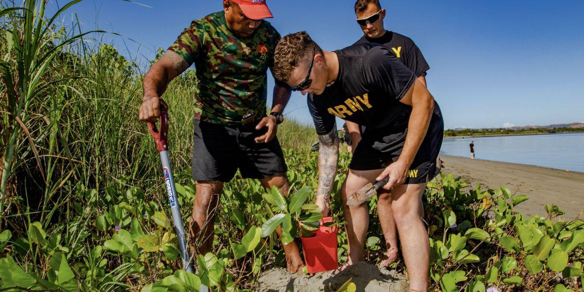 Two U.S. Army specialists join a Fijian Army sergeant in planting Dilo trees as part of a coastal and reef revitalization project in the Republic of Fiji. The U.S. Army works with local officials domestically and overseas in projects to support environmental concerns to avoid or repair damage.