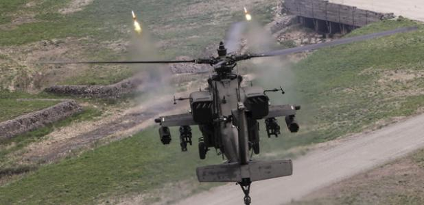 A U.S. Army AH-64 Apache fires point detonation rounds during a training exercise in South Korea. The Army intends to equip its helicopter fleet with the Small Airborne Networking Radio.