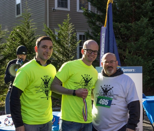 At the Young AFCEANs' run/walk for STEM in November, Gary Martin, deputy to the commanding general at U.S. Army Communications-Electronics Command (CECOM) (r), and Demetrios Chirgott, event chair (l), present first-place finisher and Young AFCEAN John Schaffer with an award.