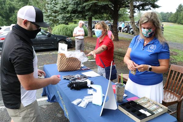 At the July event, staff at the AFCEA International Aberdeen Chapter Annual Golf Tournament support attendees as they sign in at the entrance of the Wetlands Golf Course.