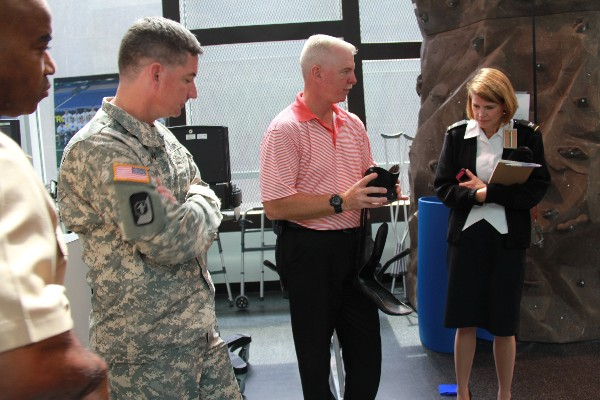 CFI program manager Stuart Campbell (c) explains advances in lightweight prosthetics engineering to Capt. John Windom, USN (far l), Col. Richard Wilson, USA, and Col. Nicole Kirkenbush, USA, during a Young AFCEAN Industry Tour in September.