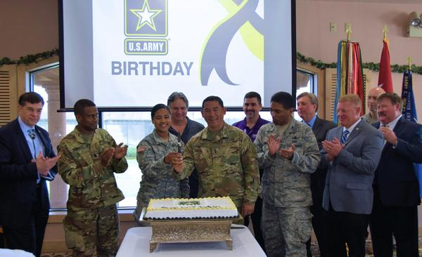 Maj. Gen. Garrett Yee, USA, acting director of Cybersecurity Directorate, Office of the Chief Information Officer (CIO)/G-6 (r, center), cuts the ceremonial cake with Spc. Aery Jackson, USA, 236th Signal company, Texas Army National Guard (l, center), in honor of the Army's 242nd birthday during the chapter's June monthly luncheon.