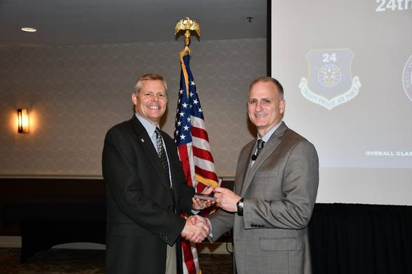 Alamo Chapter President Rick Lipsey (l), presents Robert Cole, executive director, 24th Air Force, Air Combat Command, Joint Base San Antonio-Lackland, Texas, with a coin for his presentation during the chapter's October luncheon.