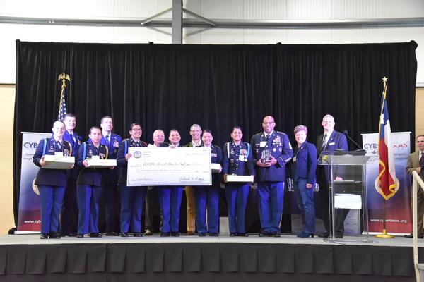 Chapter President Rick Lipsey (far r) and Vice President of Scholarships and Educational Grants Karen Rolirad (2nd to r) present the Best All Female Team, Alamo Heights Army JROTC, with $6,000 in scholarships during the 9th Annual San Antonio Mayor's Cyber Cup in March.