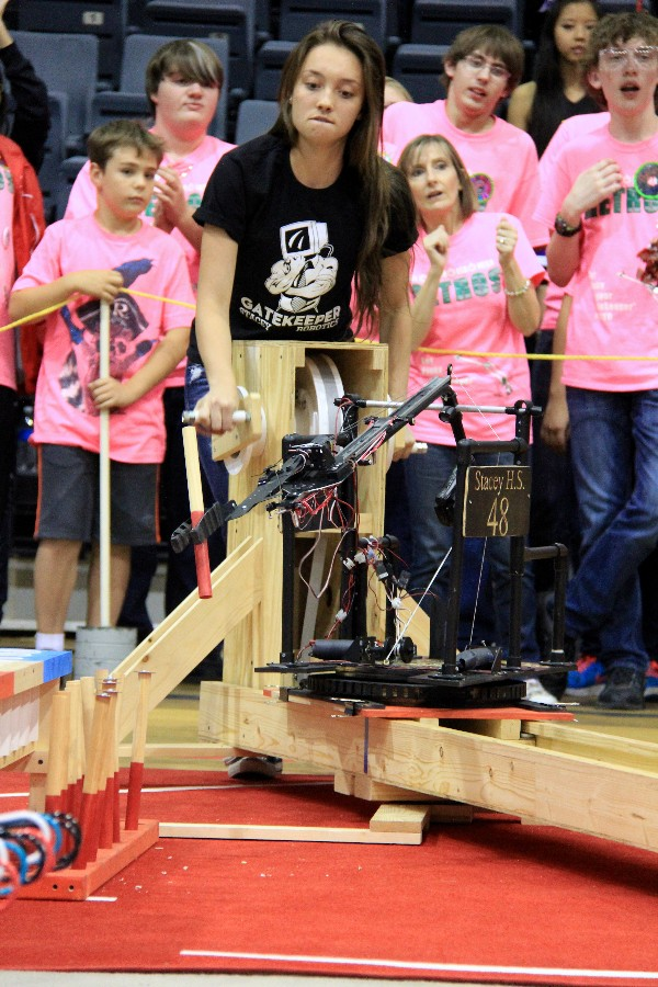 In November, Haylie D'Arrigio of Stacey High School concentrates on maneuvering her robot to pick up, grasp, and place a peg into a cup, as supporters of rival Robert E. Lee High School cheer their team on in the background.