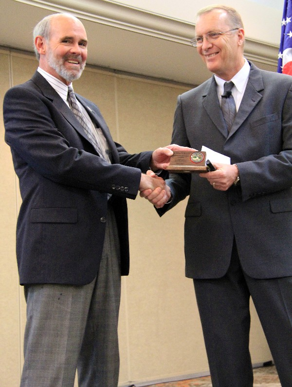 Dr. Blanton (r) accepts a token from David Kovach, chapter executive vice president, following his keynote in April.