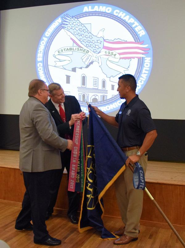 Chapter Vice President of Programs Juan Toves (r) holds the chapter flag while Vice President of Memberships Tom Allen (l) and President Rick Lipsey attach the recent Membership Growth Award streamer in July.