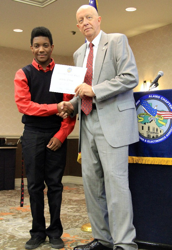 Celestin McAngy (l), a sophomore at Texas A&M University-San Antonio, accepts a $1,000 scholarship certificate from Vic Helbling, chapter board member, in September.