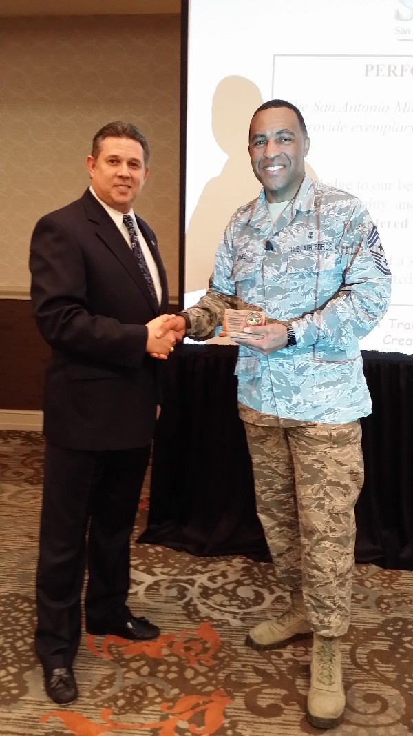 Chief Master Sgt. Maurice James, USAF, command chief master sergeant, 59th Medical Wing, accepts a thank you token from Bill Robinson, chapter board member, following Sgt. James� March keynote speech.