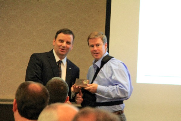Thele (l) accepts a token of appreciation from Morrow following his luncheon presentation in February.