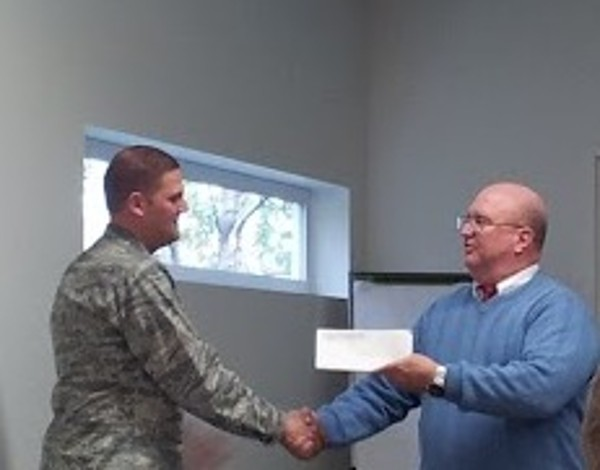 Ed Ryglewicz (r), regional vice president, presents a $1,000 STEM grant to Lt. Col. Brian Hippel, USAF, newly elected chapter president, in October.