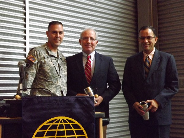 Lt. Col. Dave Elder, USA (l), chapter president, presents AFCEA mugs to Jeff Roe (c), vice president of federal marketing for General Communications Incorporated, and Anand Vadapalli, president and chief executive officer of Alaska Communications, who both spoke at the September luncheon.