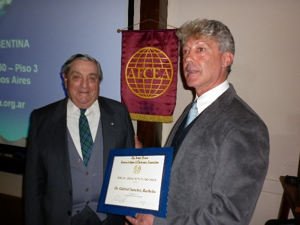 In September, Rear Adm. Emilio Nigoul, ARA (Ret.) (l), chapter president, presents a framed certificate to Gabriel Sanchez Barbeito, chapter board member, in recognition of his services to education.