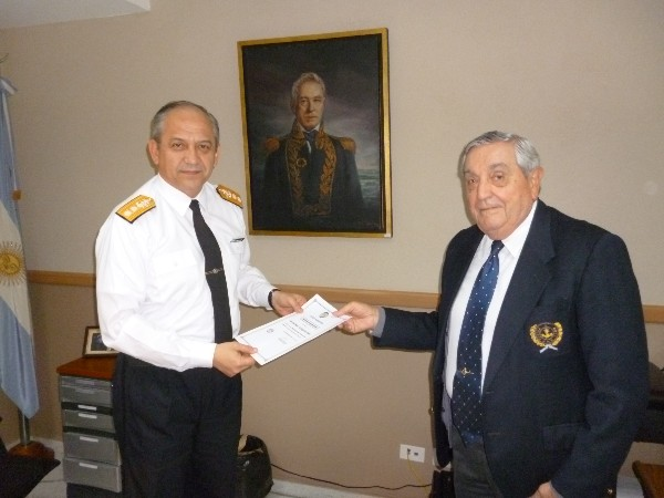 In May, Rear Adm. Emilio Nigoul, ARA (Ret.), chapter president (r) presents a check and certificate to Rear Adm. Ricardo R. Christiani, ARA, director general of education of the navy.