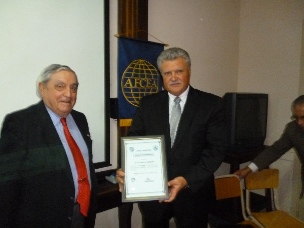 In August, Eduardo Martino (r), superintendent of communications and technical services, Metropolitan Police, receives a Distinguished Membership Award from Adm. Nigoul.