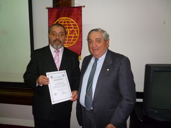 Rear Adm. Emilio I. Nigoul, ARA (Ret.) (r), chapter president, gives a certificate of recognition to Muoz in August.