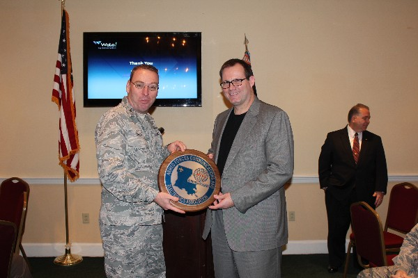 Col. Frank Simcox, USAF, chapter president, presents Rory Welch, chief executive officer of WaLa!, with a chapter plaque in appreciation for his speech at the February luncheon.