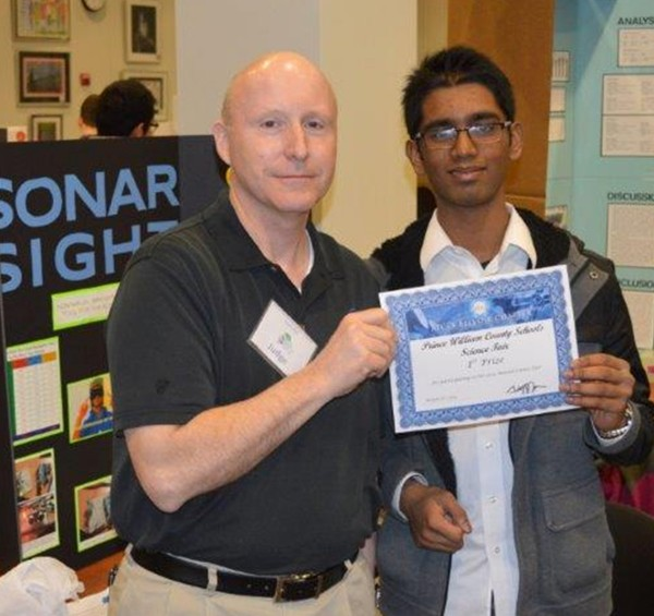 Bill Jones, chapter president, joins a student scholarship recipient during the science fair in March.