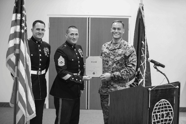 Capt. Thomas Cunningham, USMC (r), accepts a Commander's Award from Commanding General Marine Forces Reserve recognizing the chapter for support of the 2013 Marine Toys for Tots Program. Presenting the award are Gunnery Sgt. Matthew Klepsa, USMC (c), and Staff Sgt. John Farrell, USMC, from the 4th Light Armored Reconnaissance Battalion.