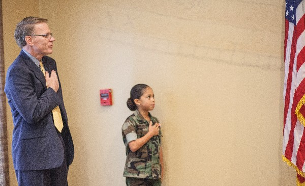 Chapter President Mark Witzel and Eagle Young Marine Pfc. Amaya Morales lead attendees in the Pledge of Allegiance to start the December chapter luncheon.