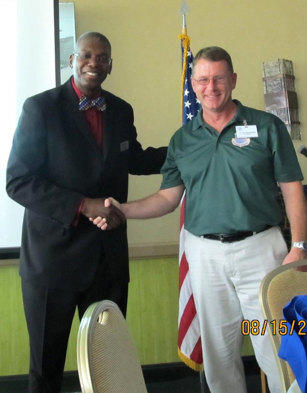 Dr. Derrick L. Tinsley (l) of Strayer University receives a chapter coin from Dan Steele, chapter president, in August.