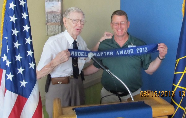 Andy Anderson (l) presents the Model Chapter Award ribbon to Steele at the August meeting.