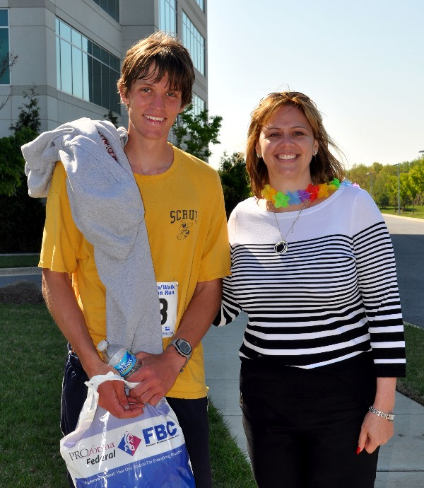 Jennifer Kauffman recognizes James Fisher, 22, of Millersville, Maryland, as the fastest finisher in the April fundraising race. He crossed the finish line with a time of 17:53.0.