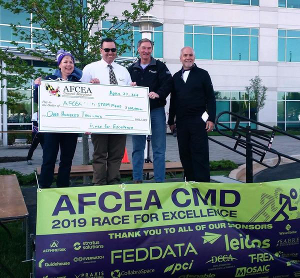Jessica Morgenstern, chapter scientific education vice president; Martin Barrett, immediate past chapter president; Roger Crone, CEO, Leidos; and Bob Mullen, chairman, Race for Excellence, present a check to the chapter's STEM scholarship fund at the April event.