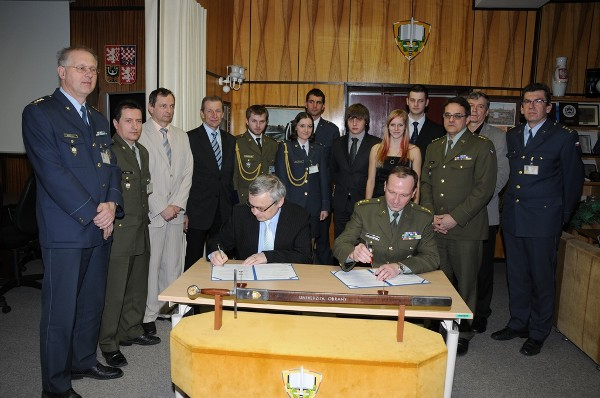 Josef Strelec, chapter president, and Col. Bohuslav Přikryl, CZA, rector of the Defense University in Brno, Czech Republic, sign a memorandum of understanding in April between AFCEA and the university, while chapter members, university representatives and members of a new student club look on. Attendees include (l-r) Col. Vlastimil Maly; Lt. Col. Petr Hruza; Miroslav Janosek, associate professor; Ladislav Nesrsta, associate professor and chapter vice president; six student club  members; Col. Martin Macko, vice rector for science and exert affairs; Brig. Gen. Rudolf Urban (Ret.), vice rector for marketing and external affairs; and Col. Libor Draan, dean, faculty of military technology.