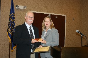 In August, Jackie Whittaker, chapter president, presents a plaque to the chapter's newest Life Member, Thomas Batty.