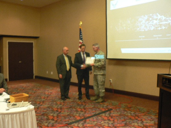 Col. Henry (r) receives a certificate of appreciation from Dan Curtis (l), chapter president, and Casey Weinstein, chapter vice president for programs, at the September meeting.