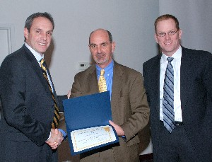 Ricky L. Peters (c), deputy director, Air, Space and Information Operations, Headquarters Air Force Materiel Command, Wright-Patterson Air Force Base, Ohio, accepts a token of appreciation from Dan Curtis (l), chapter vice president for programs, and Dave Judson (r), chapter president. Peters provided the keynote presentation at the February luncheon.
