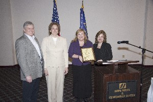 Linda Skinner, chapter director for membership, presents Deb Stanley, Dan Archibald and Billie Common, LDSS Corporation, with a commemorative plaque honoring the company's new corporate membership at the April meeting.