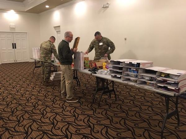 Col. Roberto R. Castillo, USA, and event attendees prepare care packages for deployed Soldiers at the December event.