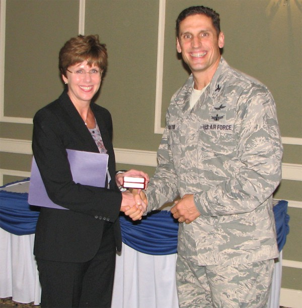 Kerry E. Kelley, director of command, control, communications, and computer systems and chief information officer, U.S. Strategic Command, receives a memento from Col. Donovan L. Routsis, USAF, chapter president, for speaking to the chapter in October.