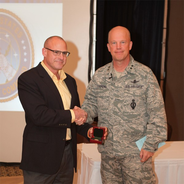 GREATER OMAHA—Kirk Bruno, chapter executive vice president, presents Maj. Gen. John W. Raymond, USAF, director of plans and policy, U.S. Strategic Command, with a chapter coin for presenting at the chapter's Heartland TechNet luncheon in May.