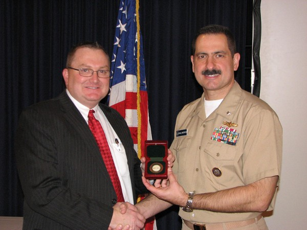 Special Agent Kenneth A. Schmutz (l), FBI, receives a token of appreciation from Cmdr. Paul Anderson, USN, chapter vice president of programs. Schmutz spoke to the general membership about cyberthreats at the March luncheon.