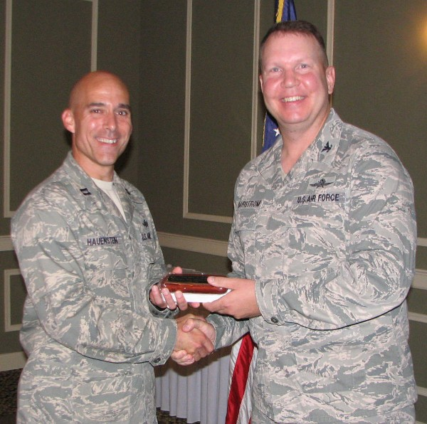 Capt. Keith Hauenstein, USAF (l), TechNet chairperson, shakes hands with Col. Bjurstrom at the June meeting. Capt. Hauenstein received the chapter's Meritorious Service Award for putting together its Heartland TechNet for 2013.