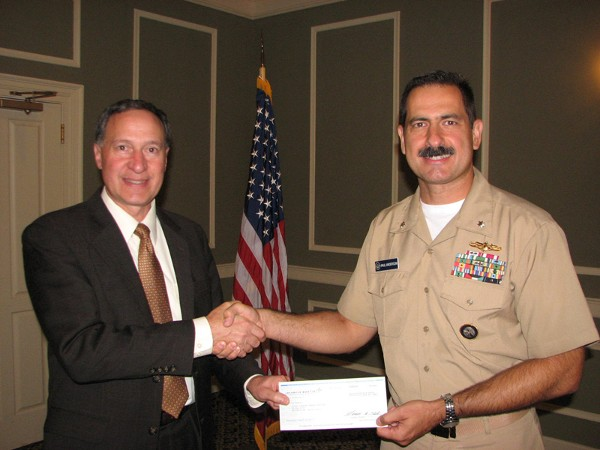 Frank Gallegos (l), senior manager, Omaha Office Corporate Business Development, Lockheed Martin, shakes hands with Cmdr. Paul Anderson, USN, chapter vice president of programs. At the September luncheon, Gallegos presented a check for $1,000 from Lockheed Martin to the chapter in support of its education fund.